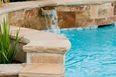 Luxurious swimming pool with stone waterfall at Toowoomba Pavers